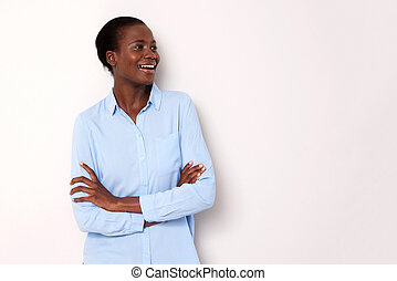 smiling african woman standing with arms crossed and looking away on white background