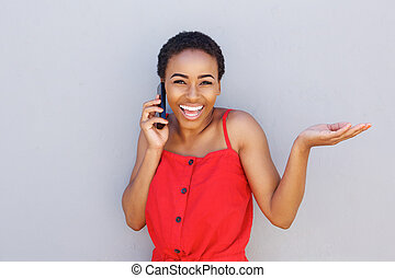 smiling african woman talking on cell phone with hand raised