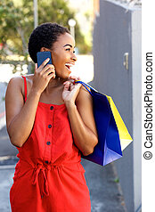 smiling african woman talking on cell phone with shopping bags