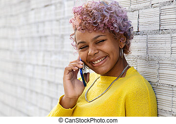 portrait of smiling afro american girl with mobile phone on the street