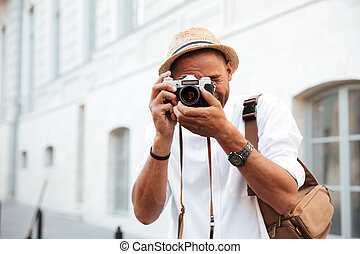 Portrait of smiling afro american man making photo on camera