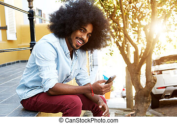 smiling afro man sitting outside by sidewalk with mobile phone