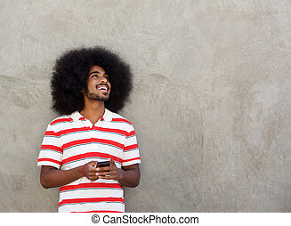 smiling afro man standing with mobile phone