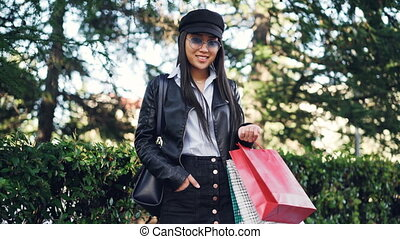 Portrait of smiling Asian girl shopaholic standing outdoors in the street with shopping bags and looking at camera. Green trees and bushes are in background.
