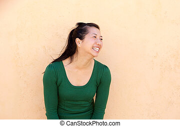 smiling asian woman in green sweater looking away