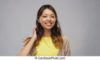 portrait of smiling asian woman touching her hair -...