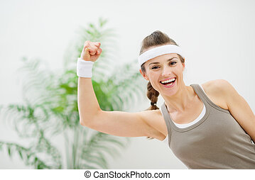 Portrait of smiling athletic woman showing biceps