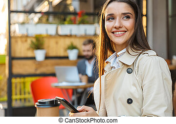 Portrait of smiling attractive woman drinking takeaway coffee and typing on mobile phone while sitting in cafe
