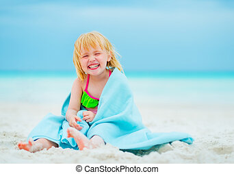 Portrait of smiling baby girl in towel sitting on beach