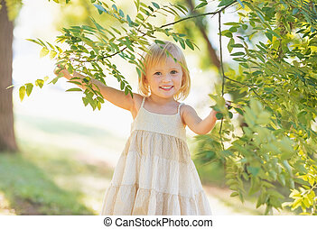 Portrait of smiling baby girl looking out from tree foliage