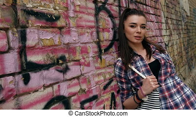 Portrait of smiling beautiful fashion woman in checkered shirt and with pony tail against graffiti wall