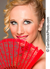 Portrait of smiling beautiful girl with textile fan