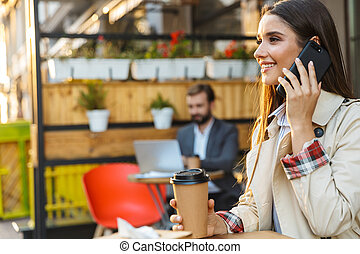 Portrait of smiling beautiful woman drinking takeaway coffee and talking on mobile phone while sitting in cafe