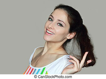 Portrait of smiling beautiful woman holding hair and looking in