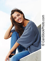smiling beautiful young woman sitting outside