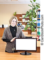 Portrait of smiling beautiful young woman with blank computer monitor