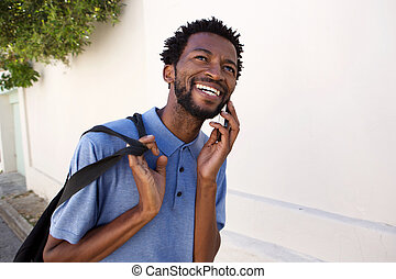 smiling black man walking outside on telephone call