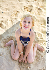 Portrait of smiling blond girl sitting in swimwear on beach