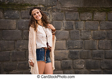 portrait of smiling boho young woman near stone wall