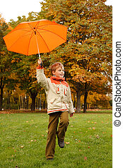 Portrait of smiling boy in autumn park. In hand umbrella, looks aside.