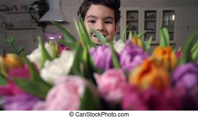 Portrait of smiling boy with bouquet of flowers - Closeup...