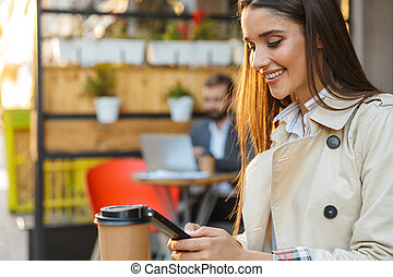 Portrait of smiling brunette woman drinking takeaway coffee and typing on mobile phone while sitting in cafe
