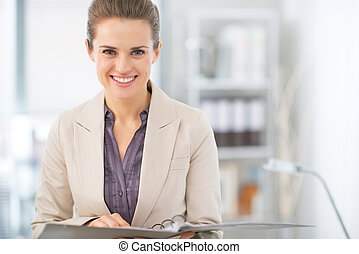 Portrait of smiling business woman with documents in office