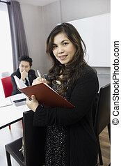 Portrait of smiling business woman with notebook in the office