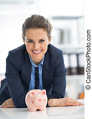Portrait of smiling business woman with piggy bank