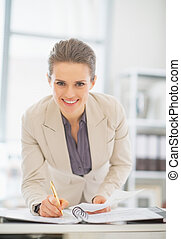 Portrait of smiling business woman working in office with documents