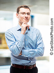 Portrait of smiling businessman in blue striped shirt in office