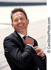 Portrait of smiling businessman sitting adjusting his tie