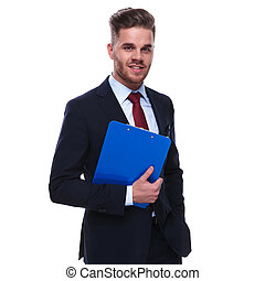 portrait of smiling businessman with folder in hand standing
