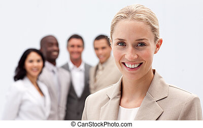 Portrait of smiling businesswoman in front of her team -...