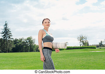 caucasian woman with yoga mat