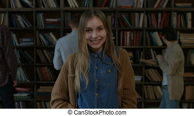 Portrait of smiling charming girl in library