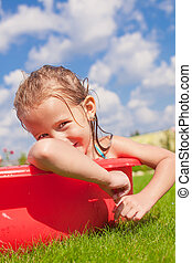 Portrait of smiling charming little girl enjoying her vacation in the pool outdoors