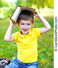 Portrait of smiling child boy with book on the grass in summer day