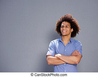 smiling confident man standing with arms crossed