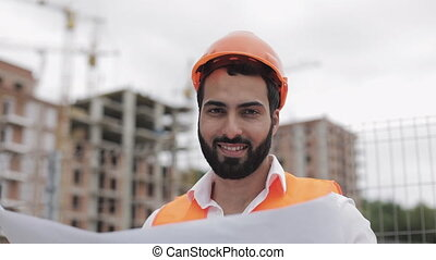 Portrait of smiling construction worker in orange helmet looking at the camera. The builder with construction project stands on the construction site background. Slow motion.