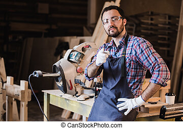 portrait of smiling construction worker pointing with finger at camera