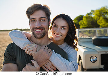 Portrait of smiling couple by vehicle