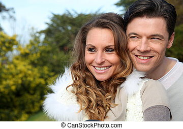 Portrait of smiling couple sitting outside on a sunny day