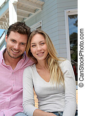 Portrait of smiling couple standing in front of house