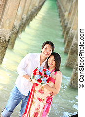 portrait of smiling couples under the pier on the beach