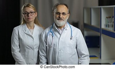 Portrait of smiling doctos in hospital office - Successful...