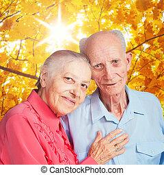 Portrait of smiling elderly couple on autumn landscape -...