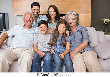 Portrait of smiling extended family on sofa in living room