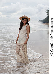 portrait of smiling face of young asian woman with long dress and fashion wide straw hat standing on sea beach