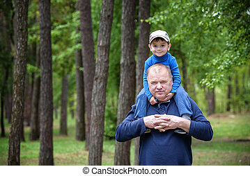 Portrait of smiling father giving his son piggyback ride outdoors against spring or summer forest  park